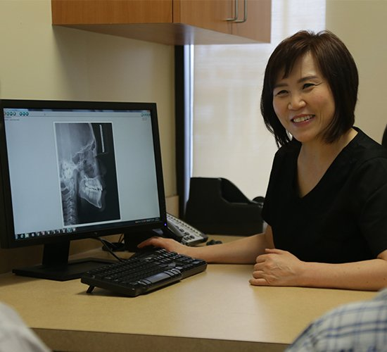 Dr. Lee showing patient x-rays in consultation room