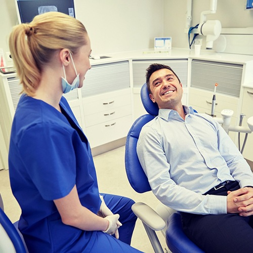 man sitting in dental chair and smiling at dentist