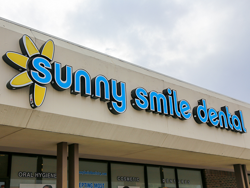 Sunny Smile Dental sign on office building
